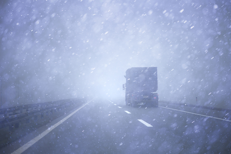 driving conditions: Truck vehicle at highway road during a heavy snowfall and rainfall. Dangerous lorry driving at bad weather conditions.