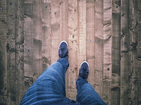 foot bridges: Top view of a man walking on wooden textured bridge floor with copy space background.
