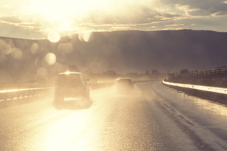 dui: Car driving on rainy wet and sunny highway with traffic. Personal perspective used. Stock Photo