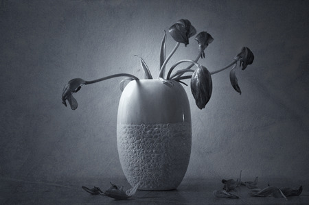 Stil: Grunge Wilted flowers in vase illustrates mourning, loss and grief. Textured, monochrome stil life.