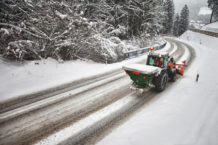 heavy snow: Tractor deicing and cleaning a road in winter.
