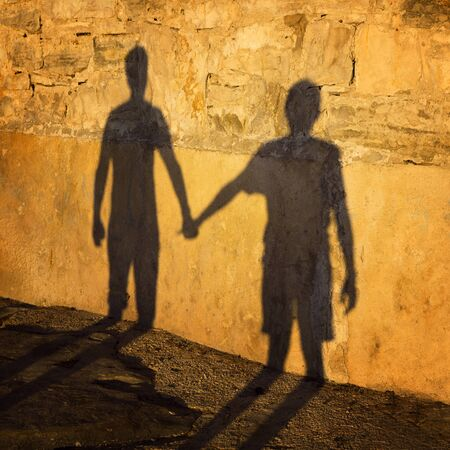 people shadow: Silhouette background, shadow of two people holding hands. Sunset light used. Stock Photo