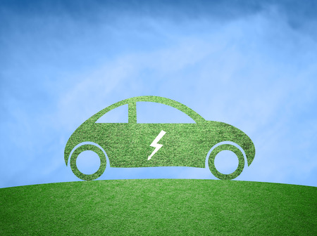 clean sky: Concept electric car background. Green grass textured flat car icon with electric symbol on clean blue sky background. Stock Photo