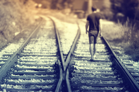 A men walking alone down the railway tracks. Selective focus used. Hopeful walking on rails