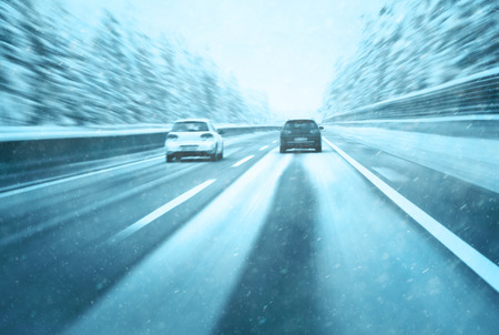 overtaking: Conceptual blurry safety car overtaking on snowy highway. Motion blur visualizes the speed and dynamics.