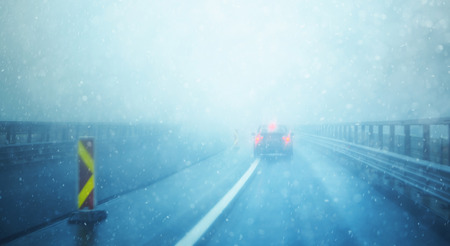 Abstract blurred car on dangerous, foggy and slippery highway in heavy storm weather. Winter snowy conditions on the highway. Motion blur visualizes the speed and dynamics.