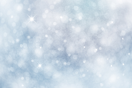 Artistic winter snowfall bokeh background with sparkle. Silver and soft blue colored blurry Christmas and New Year greeting card illustration background with sparkle.