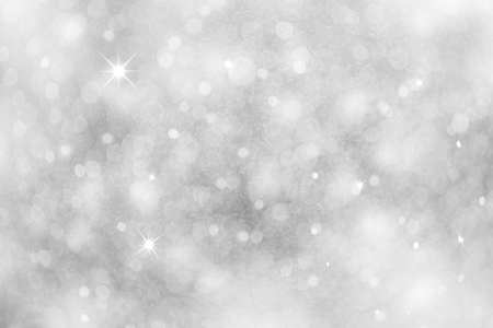 Artistic winter snowfall bokeh background with sparkle. Silver colored blurry Christmas and New Year greeting card illustration background with sparkle.