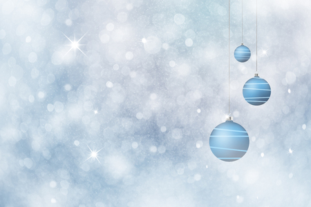 Beautiful blue Christmas decoration bulbs set on abstract blurred silver blue colored snowfall bokeh background. Beautiful New Year and Christmas holiday greeting card background. Stock Photo