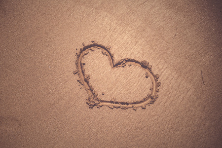 Love heart sign drawn by hand on sunny sandy beach. Vintage filter effect used.