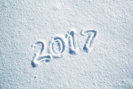 Happy new year 2017 celebration message handwritten on the sunny fresh snow. Lovely Happy new Year Holiday greeting card.
