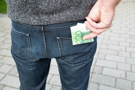 Outside in the park a man is putting money of one hundred euros in his back pocket.