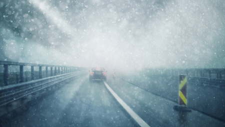 Abstract blurred car on dangerous, foggy and slippery highway in heavy snowstorm weather. Winter snowy conditions on the highway. Motion blur visualizes the speed and dynamics.