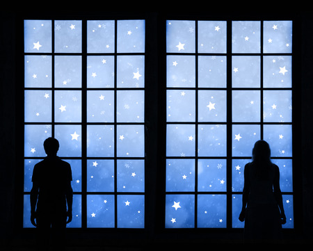 Silhouette of a couple standing and looking through big window at blue colored Winter holiday star shape decoration background. Couple with Christmas and New Year wishes background.