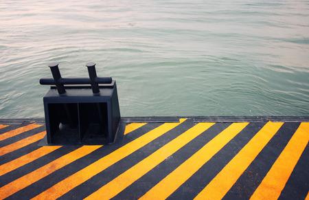 Black mooring bollard on sea docks.