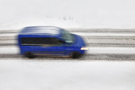 carefully: Carefully driving of a vehicle on the heavy snow road. Motion blur (long time exposure) visualizies the speed and dynamics. Stock Photo