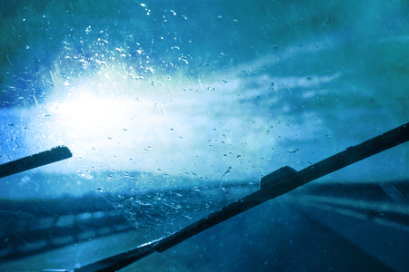 personal perspective: Dangerous blurry driving car in the stormy and slippery road. Rain through windshield of moving car on highway. Car windshield wipers on in the rainy weather. Personal perspective used. Stock Photo