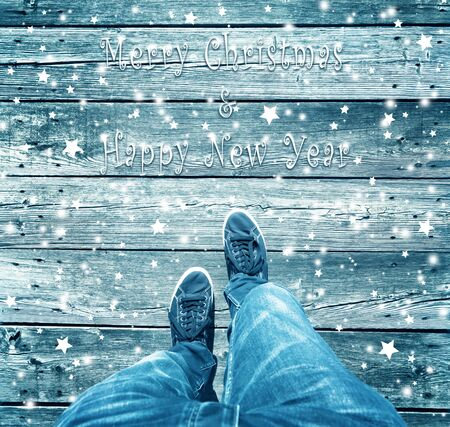 Merry Christmas and Happy new year man walking. A man walk and crossing blue colored Xmas decoration wooden bridge, point of view perspective used. Conceptual Christmas and New Year Holiday greeting card background.