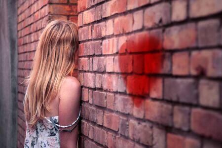 atractive: Sad blonde woman in summer dress stand leaning against a old brick wall with painted red heart symbol. Selective focus used.