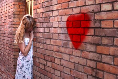 atractive: Lonely blonde woman in summer dress stand leaning against a old brick wall with painted blurry red heart symbol. Selective focus used.