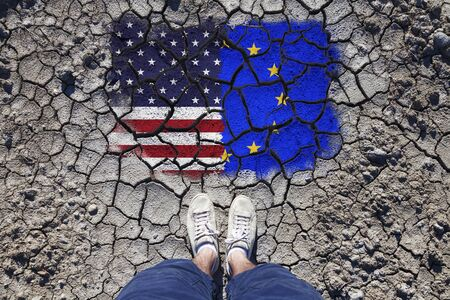 craked: Point of view of a man standing on cracked soil with torn United States of America and European union flags. Stock Photo