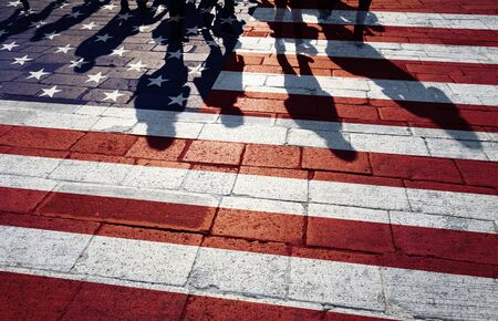 border patrol: Shadows of group of people walking through the streets with painted Usa flag on the floor. Concept political relations with neighbors.