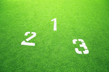 Conceptual winners podium with first, second and third place numbers on green soccer or football field grass background. Stock Photo