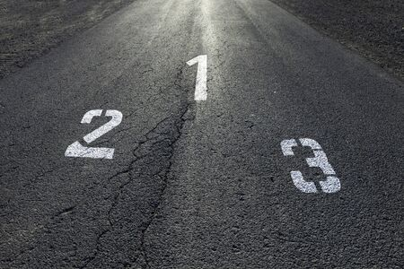second floor: Sunny straight race asphalt road with painted first, second and third place numbers on the floor.