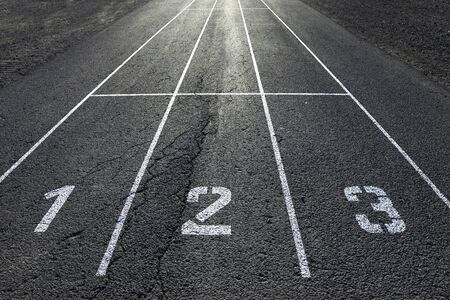 second floor: Sunny straight race asphalt road with painted lines and first, second and third place numbers on the floor. Conceptual roadway competition background.