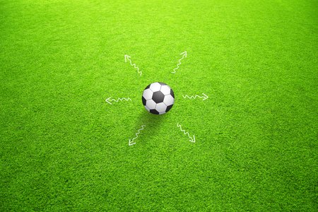 Soccer game strategy plan concept or football field with one soccer ball and the all directions marked of movement. Game soccer strategy plan team on sunny green grass background.