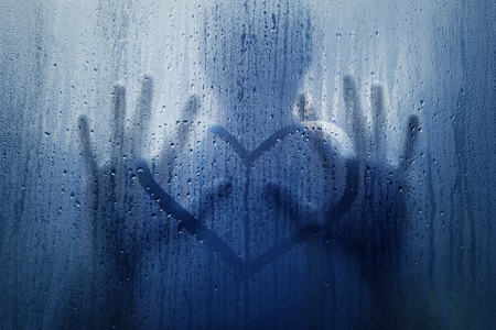 Silhouette of a man in love touching hand drawn heart symbol on the wet rainy glass window. Blue color tone filter used.