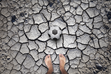 Soccer ball on soil drought cracked football field with barefoot player legs. Personal perspective used.