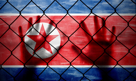 Conceptual prohibited area security fence with North Korea flag painted on the grunge background and human hands.  Stock Photo