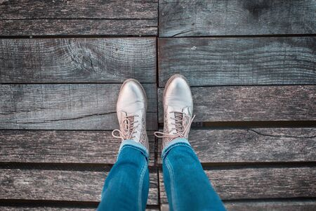 foot bridges: Top view of woman in jeans with shoes standing on the aged wooden floor. Personal perspective used.