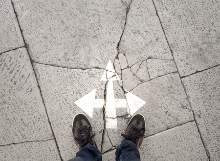 Concept business person standing on the cracked and damaged stone ground at crossroads. Conceptual business start decision and choice background. Point of view perspective used.