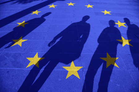 illegals: European Union flag painted on tiled street floor and shadows group of people walking at sunny day. Stock Photo
