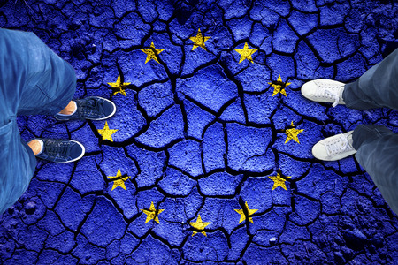Top view of a people standing on damaged cracked soil ground with painted European Union flag. Point of view perspective used. Conceptual EU disintegration background. Stock Photo