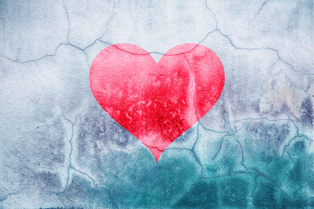 Broken red heart sign painted on cracked wall background. Stock Photo