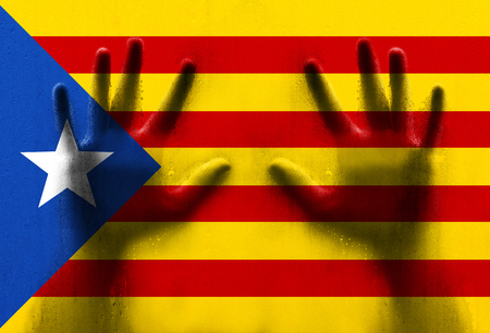 Catalonia flag with human hands on wet window.