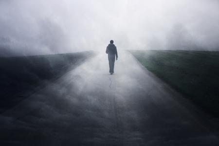 Man walking alone on dark misty foggy asphalt road.