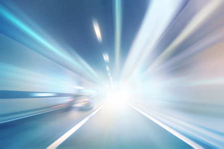 Abstract blurred high speed car driving in the highway tunnel. Motion blur visualizes the speed and dynamics. Personal perspective used.