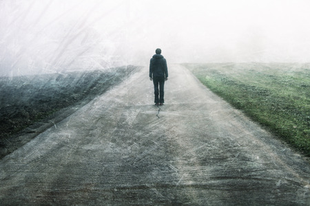 Man standing and gazing on rural foggy and misty grunge textured asphalt road. Stock Photo