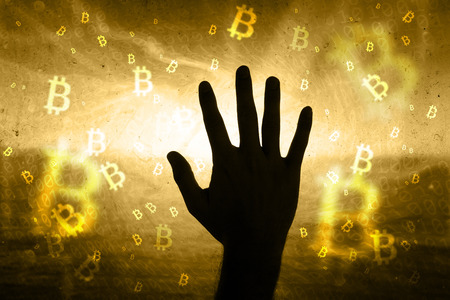 Grunge glass with silhouette of a person hand on a abstract bitcoin sign motion blurred background. Stock Photo