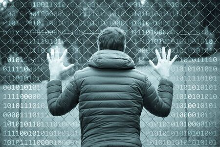 Man standing and holding his hands on fence. Binary numbers background.