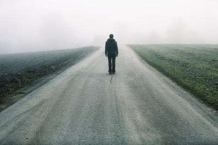 Man standing alone on rural foggy and misty asphalt road.