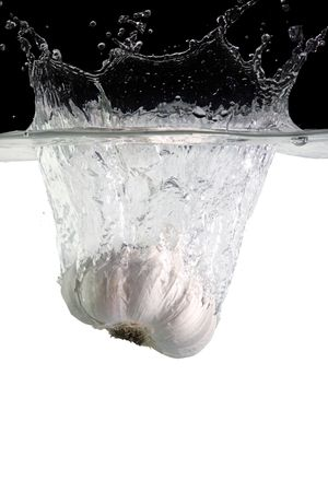 garlic thrown in water with black and white background Stock Photo