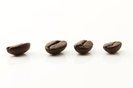 closeup of four coffee beans on white background