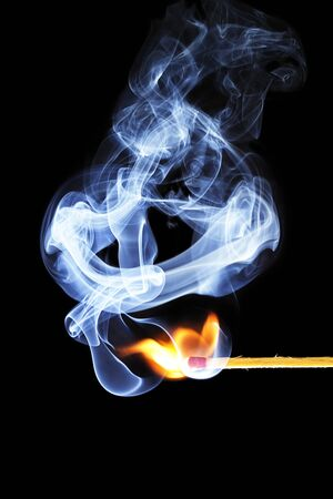one match is igniting in front of black background with blue smoke photo