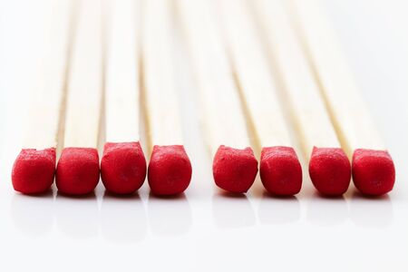 closeup of some red match heads on white background photo