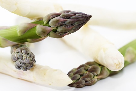 closeup of some green and white asparagus on white background